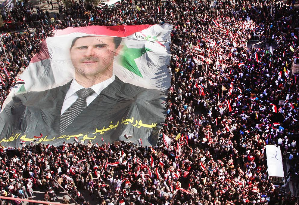 Pro-Syrian regime protesters carry a huge portrait of Syrian President Bashar Assad during a demonstration to show their solidarity with their president, in Damascus, Syria, on Sunday Nov. 20, 2011. Residents in the Syrian capital awoke to two loud explosions Sunday amid reports from activists that the Damascus headquarters of the ruling Baath party had been hit by several rocket-propelled grenades.  But eyewitnesses said the party headquarters appeared intact and reported no significant security deployment around it. (AP Photo/Bassem Tellawi)