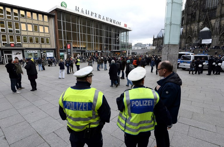 Police officers survey the area in front of the main train station and the Cathedral in Cologne, western Germany, on January 6, 2016, where dozens of apparently coordinated sexual assaults were perpetred against women on New Year's Eve.  / AFP / Roberto Pfeil