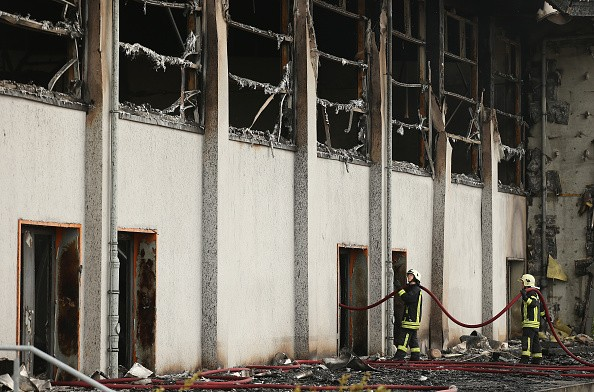 NAUEN, GERMANY - AUGUST 25:  Firemen extinguish the last embers from a fire that struck a sports hall that was intended to house refugees and migrants applying for aslyum in Germany on August 25, 2015 in Nauen, Germany. Police announced they have ruled out a technical source as causing the fire and are assuming arson is to blame. Germany has seen a spate of protests, arson attacks and violence in recent weeks from right-wing groups opposed to Germany accepting more refugees. German authorities recently announced they expct 800,000 refugees and migrants to arrive in the country this year, many of them from war-torn countries including Syria, Iraq and Afghanistan.  (Photo by Sean Gallup/Getty Images)