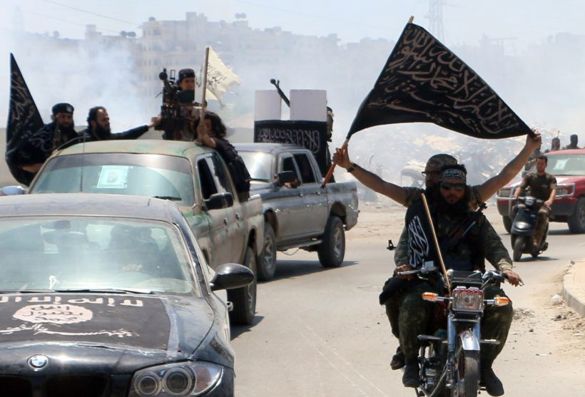 Fighters from Al-Qaeda's Syrian affiliate Al-Nusra Front drive in the northern Syrian city of Aleppo flying Islamist flags as they head to a frontline, on May 26, 2015. Once Syria's economic powerhouse, Aleppo has been divided between government control in the city's west and rebel control in the east since shortly after fighting there began in mid-2012. AFP PHOTO / AMC / FADI AL-HALABI / AFP / AMC / Fadi al-Halabi