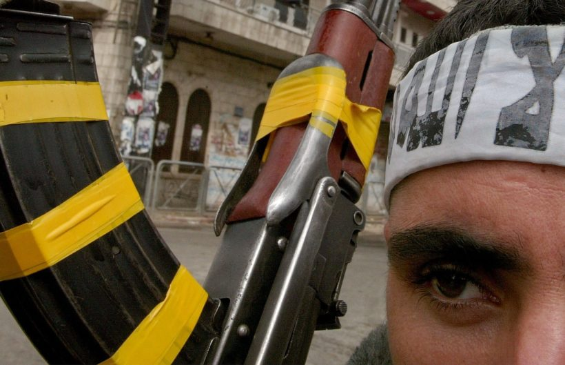 """RAMALLAH, WEST BANK - MARCH 14:  Nizar, a 21-year-old Palestinian gunman, wears a scarf on his forehead with the Arabic mantra """"There is no God but Allah and Mohammed is his prophet"""", as he totes his AK-47 assault rifle in Manara Square during fighting with Israeli soldiers March 14, 2002 in the West Bank town of Ramallah. Israeli Prime Minister Ariel Sharon ordered his troops to regroup on the outskirts of the town ahead of the visit of U.S. peace envoy Anthony Zinni.  (Photo by David Silverman/Getty Images)"""