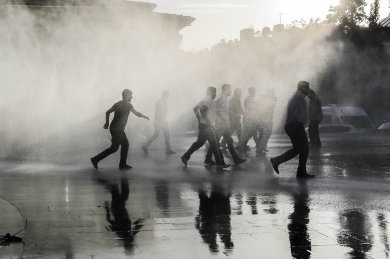 Turkish anti riot police use water cannon to disperse people who gathered after a rocket hit a mosque on April 24, 2016 in Kilis.  Two rockets fired into Turkey from an area of Syria controlled by the Islamic State group hit the border town of Kilis on Sunday, leaving 16 people injured, media reports said.  / AFP PHOTO / YASIN AKGUL