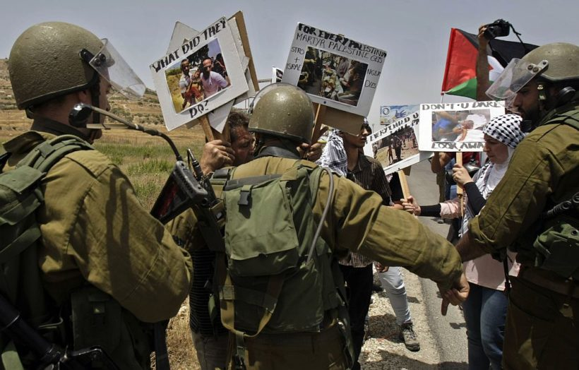 Israeli soldiers stop Palestinians during a demonstration against Israeli military action in Gaza, near the West Bank town of Nablus, Saturday,July 12, 2014. Israeli airstrikes in Gaza hit a mosque and a center for the disabled where two women were killed Saturday, raising the Palestinian death toll from the offensive to more than 125, Palestinian officials said. (AP Photo/Nasser Ishtayeh)