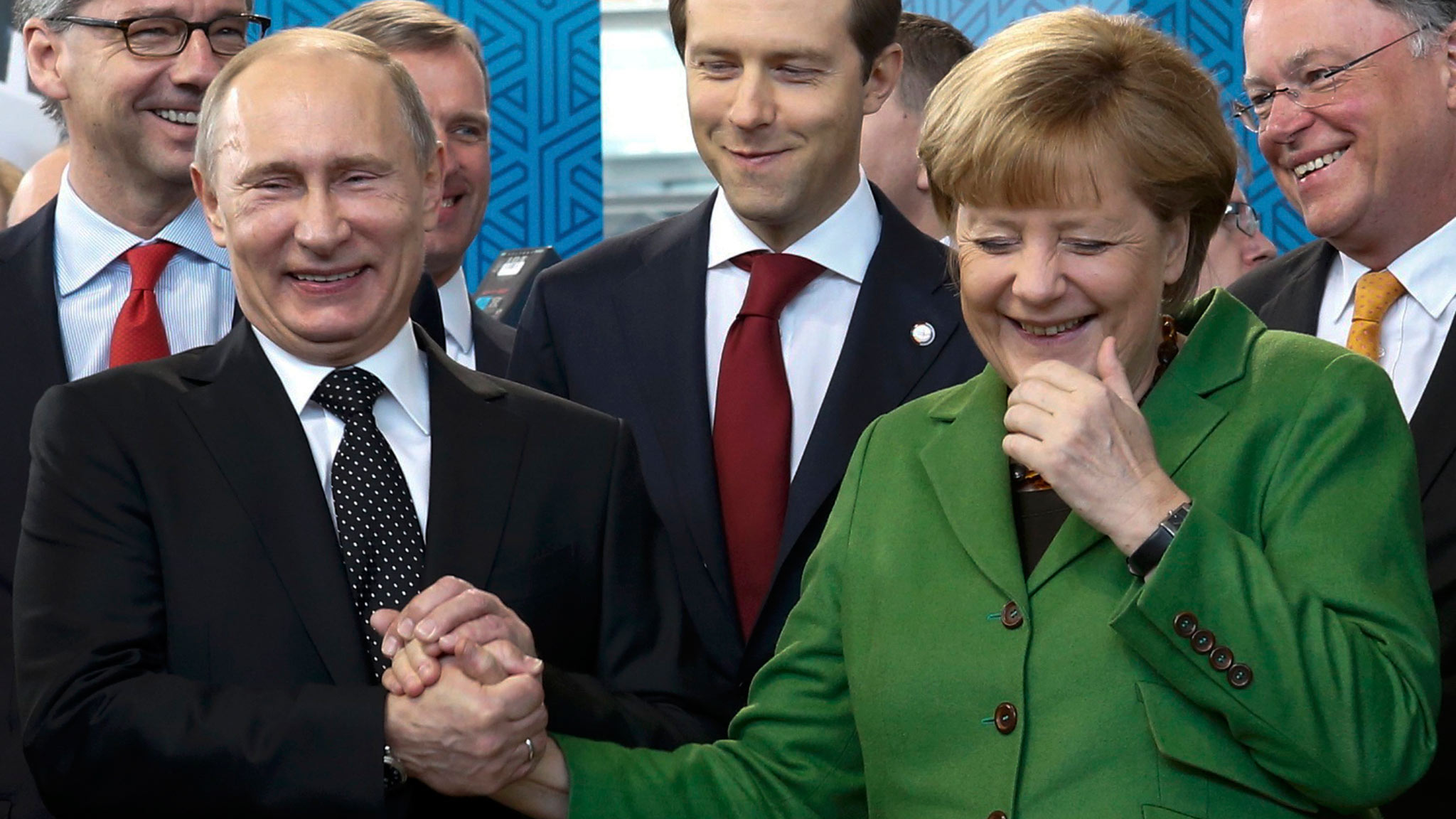 Russian President Vladimir Putin holds the hand of German Chancellor Angela Merkel as they visit the Russian booth during a tour through the Hanover Messe on the first day of the industrial trade fair, in Hanover April 8, 2013.  Russia is the partner country of the Hanover fair 2013, which runs from April 8 -12. REUTERS/Fabrizio Bensch (GERMANY  - Tags: POLITICS BUSINESS)