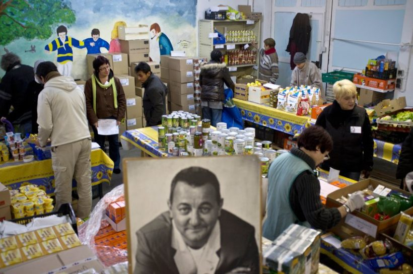 "A poster of  French entertainer Coluche, founder in 1985 of French charitable organisation 'Les Restos du Coeur' (Restaurants of the Heart) is displayed on November 28, 2011 in Villeurbanne, centraleastern France,as  people arrive to take food in a ""Resto du Coeur"", some hours after the launching of the 27th winter campaign. Some 60,000 volunteers are expected to participate in the 2011-2012 charity campaign to distribute food to the needy. Les Restos du Coeur, welcomed last year some 860,000 people and provided 109 millions of meals. AFP PHOTO / JEAN-PHILIPPE KSIAZEK"