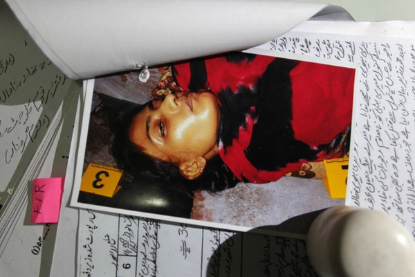 """In this photo taken on Thursday, Sept. 1, 2016, a picture of Tasleen, who was slain by her brother, is seen with police records at police headquarters in Lahore, Pakistan. Tasleem was shot dead by her brother, Mubeen Rajhu who couldn't stand the teasing, accusations and whispers from co-workers and neighbors that his sister was having an affair and with a Christian. The taunts were relentless. """"What kind of a man are you?"""" his workmates at the coal-fired steel mill where he had worked for nearly four years asked. His neighbors sneered as he passed. """"Do you have no honor?"""" they asked. (AP Photo/K.M. Chaudary)"""