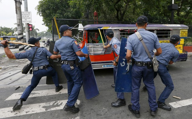 Police officers hit fleeing protesters during a violent dispersal outside the U.S. Embassy in Manila, Philippines Wednesday, Oct. 19, 2016. A Philippine police van rammed into protesters, leaving several bloodied, as an anti-U.S. rally turned violent Wednesday at the American embassy in Manila. (AP Photo/Bullit Marquez)